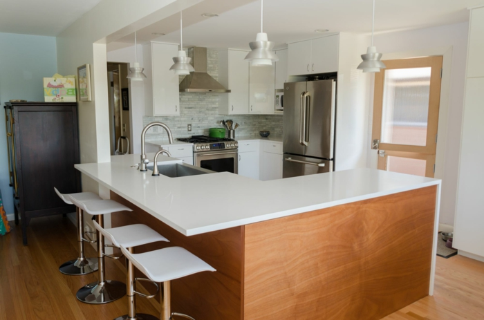 wooden kitchen island, white cabinets with white countertops, mid century modern floor tile, light grey tiles backsplash