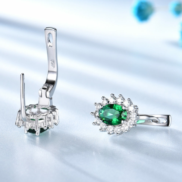 silver earrings with emerald crystals and rhinestones, traditional wedding anniversary gifts, placed on white surface
