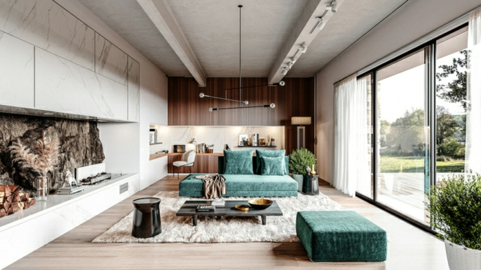 turquoise sofa and ottoman, wooden floor with white carpet, accent marble and wooden walls, interior design ideas for living room