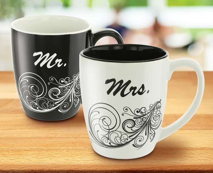 two coffee mugs, black and white for the mr and mrs, 40th anniversary gifts, placed on wooden surface