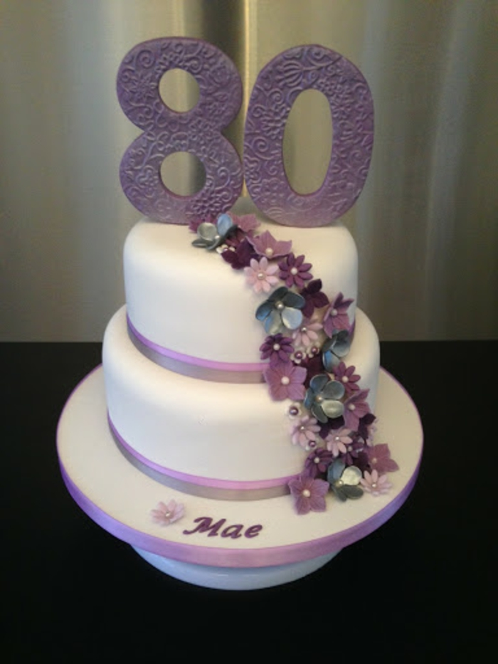 two tier cake, covered with white fondant, 80th birthday party favors, decorated with purple flowers