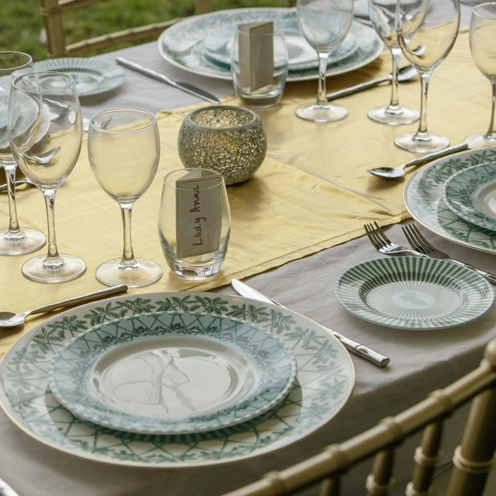 china dinner set, placed on table with grey tablecloth and gold table runner, wedding anniversary gifts by year, wine glasses and utensils