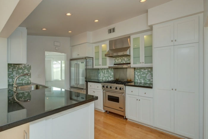 green and white mosaic backsplash, mid century modern floor tile, white cabinets with black countertops