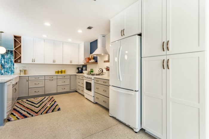 mid century modern backsplash tile, light grey cabinets with white countertops, tiled floor with rug