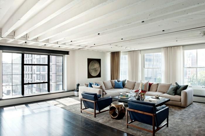 white corner sofa, two black leather armchairs, modern living room decor ideas, dark wooden floor with grey carpet