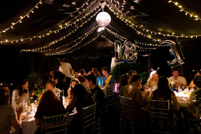 people sitting around round tables, 18th birthday ideas for boys, tulle and fairy lights hanging from the ceiling