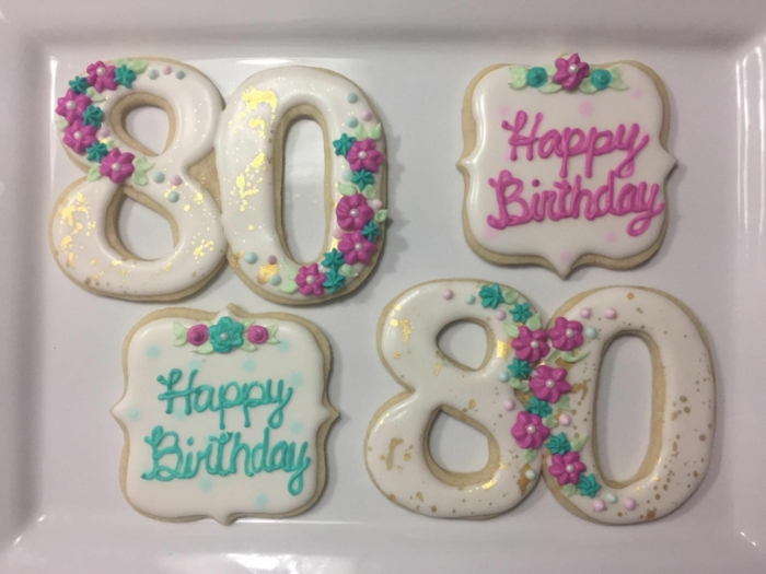 four cookies, two in the shape of number 80, 80th birthday party favors, decorated with purple flowers