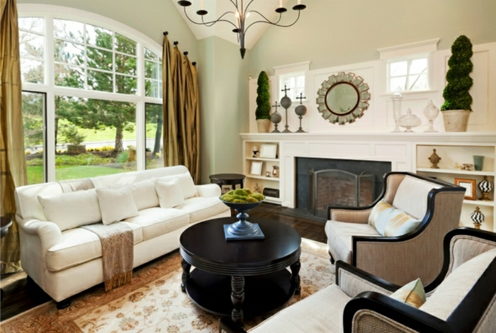white sofa and armchairs, luxury living room furniture, black wooden round coffee table, coloful carpet