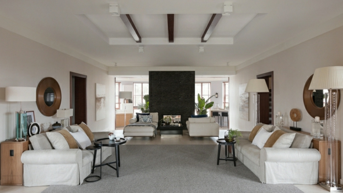 white sofas, small black coffee tables, contemporary living room furniture, wooden floor with grey carpet