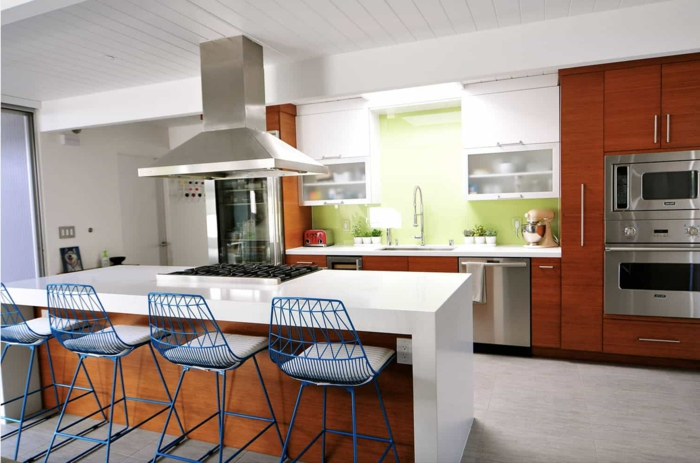wooden kitchen island, wooden cabinets with white countertops, blue bar stools, mid century modern backsplash tile