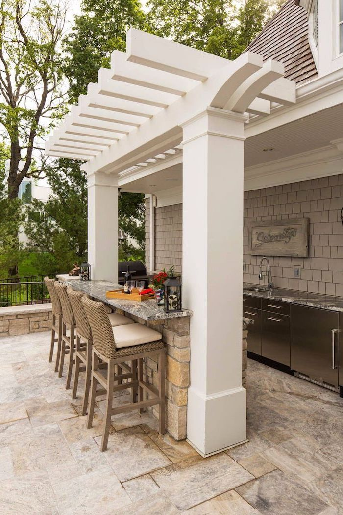 backyard kitchen bar made of stones with marble countertops tall bar stools kitchen cabinets and sink with marble countertop