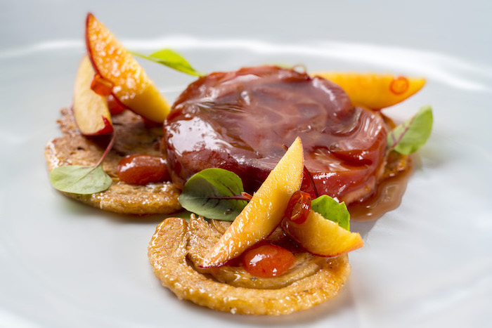 baked peaches with sweet jam sauce no bake desserts decorated with small leaves arranged on white plate