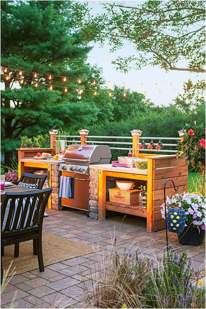 barbecue grill with wooden open shelves and stone countertops outdoor kitchen ideas wooden table and chairs tiled floor