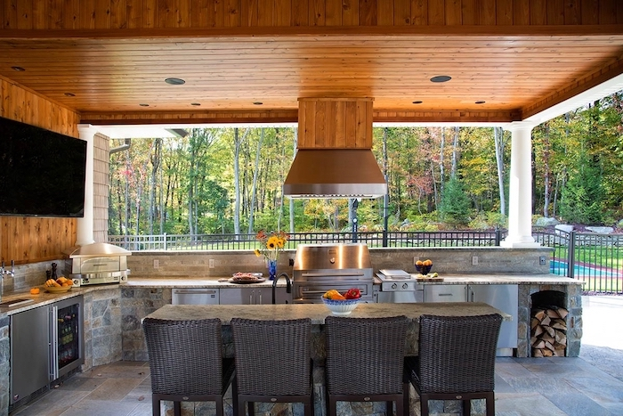black chairs around table made of stone modern outdoor kitchen made of stone with grill fridge and cabinets wooden ceiling