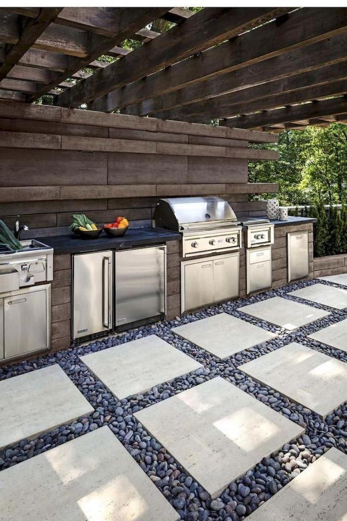 black countertop metal sink cabinets fridge grill covered outdoor kitchen stone tiles on the floor surrounded by small stones