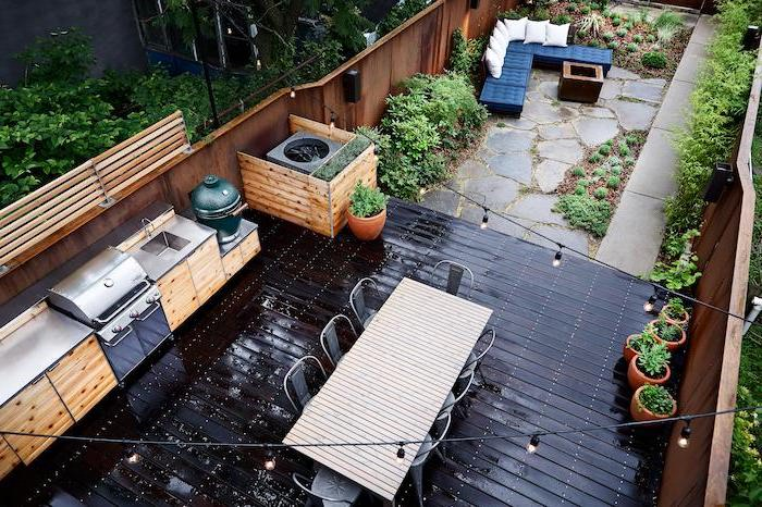 black floor with wooden cabinets and metal countertop covered outdoor kitchen long dining table and black chairs