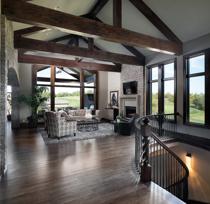 wooden floor, exposed wooden beams on white ceiling, farmhouse living room, furniture set in front of a fireplace