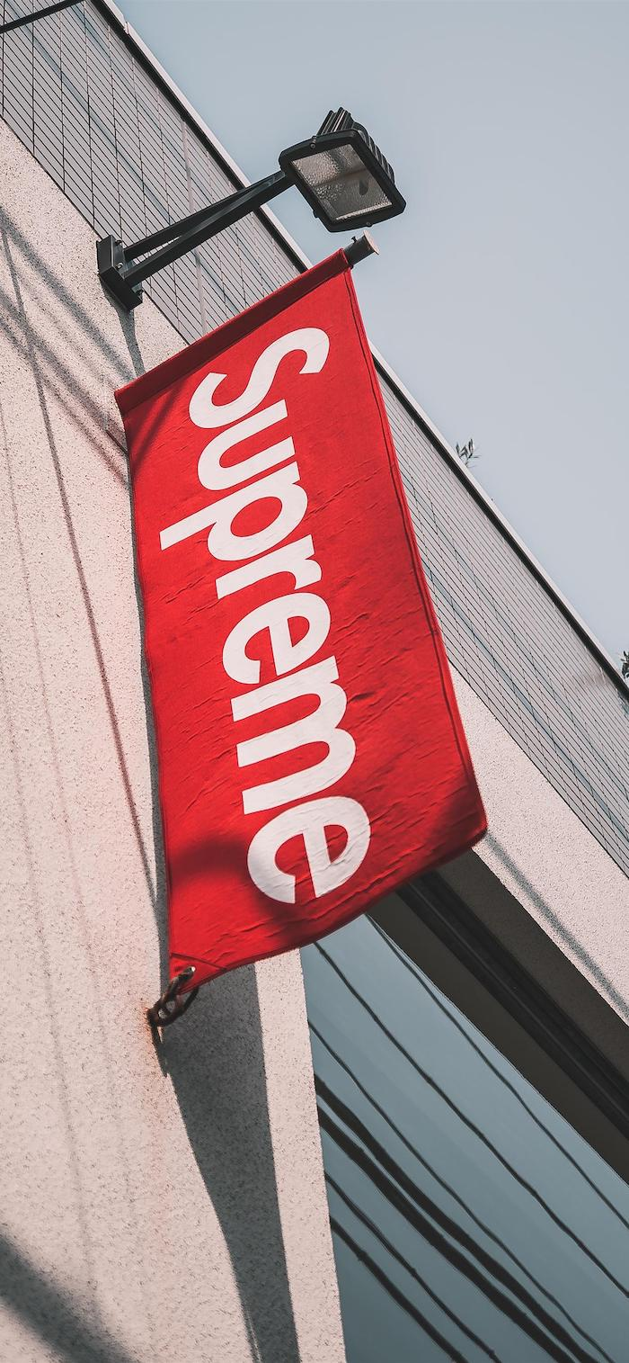 black supreme wallpaper photo taken outside of supreme store with a flag of the logo in red and white