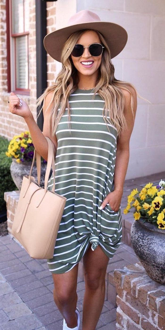 blonde woman wearing beige hat and leather bag summer outfits for women green white striped dress tied at the bottom