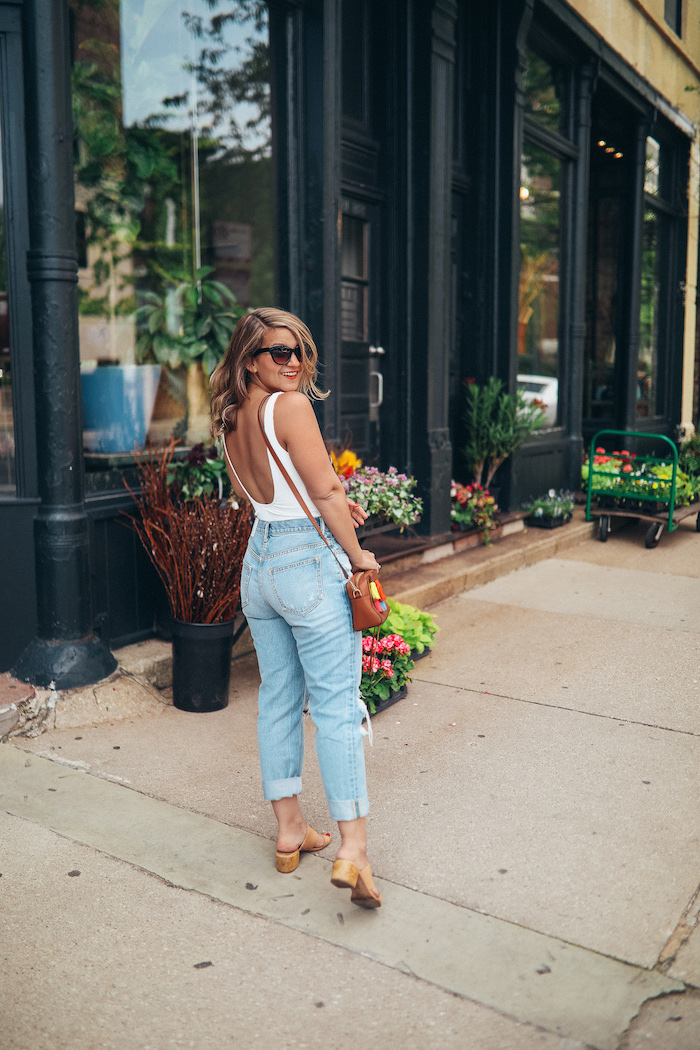 blonde woman wearing jeans and white top with bare back cute summer outfits for teens brown leather crossbody bag and sandals