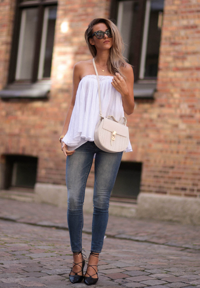 blonde woman wearing jeans white strapless top cute simple outfits black heels white bag sunglasses