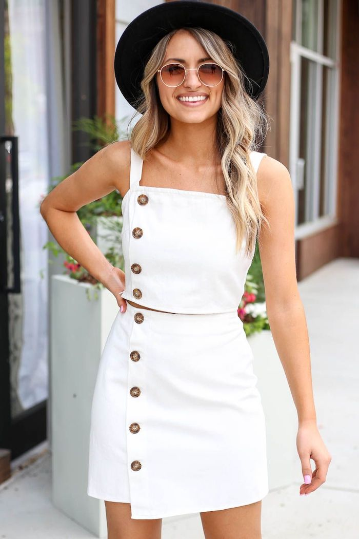 blonde woman wearing white skirt and crop top with brown buttons black hat sunglasses summer outfits
