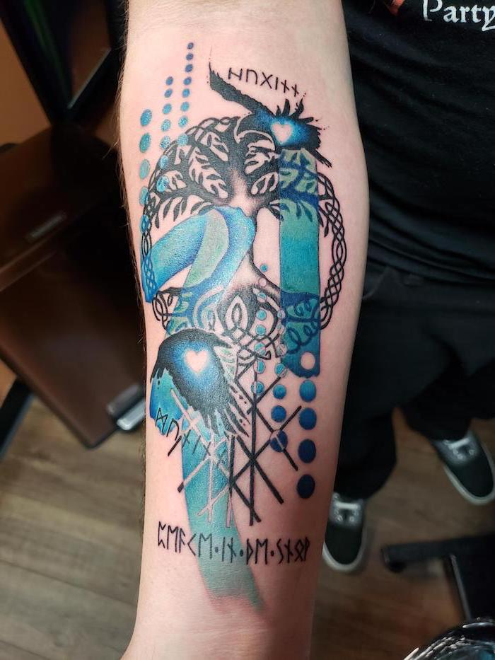blue and black tree of life forearm tattoo polka tattoo style on man wearing black t shirt jeans