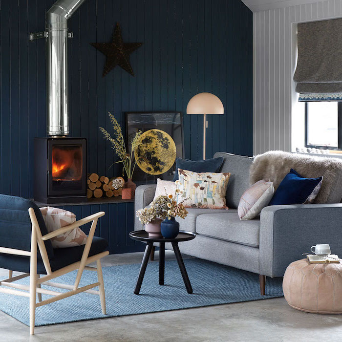 farmhouse decor, blue wooden accent wall, blue armchair and grey sofa, blue carpet on granite floor