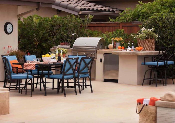 blue chairs around black dining table outdoor grill station barbecue and fridge stone countertops tiled floor