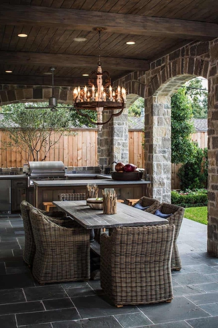 blue cushions on chairs around wooden dining table covered outdoor kitchen stole columns and floor wooden ceiling