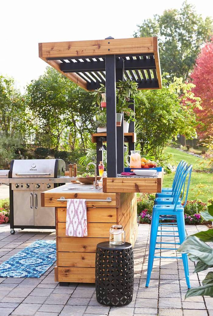 blue metal bar stools l shaped outdoor kitchen wooden kitchen island with sink metal grill reclaimed setts on the floor