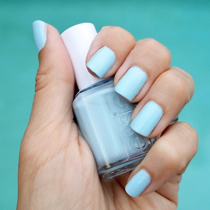 light blue nail polish, short square nails, hand holding a nail polish bottle, turquoise background