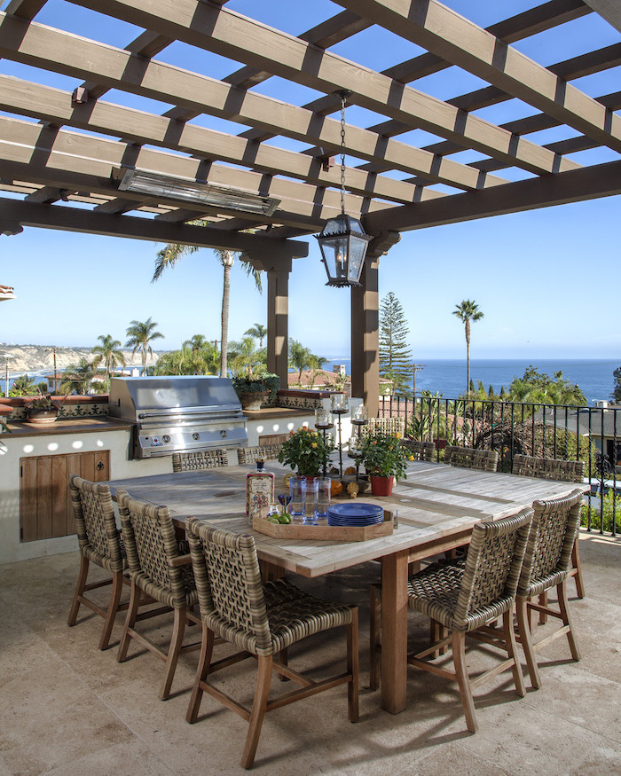 blue plates on large wooden table with chairs patio overlooking the sea modern outdoor kitchen wooden cabinets under the grill