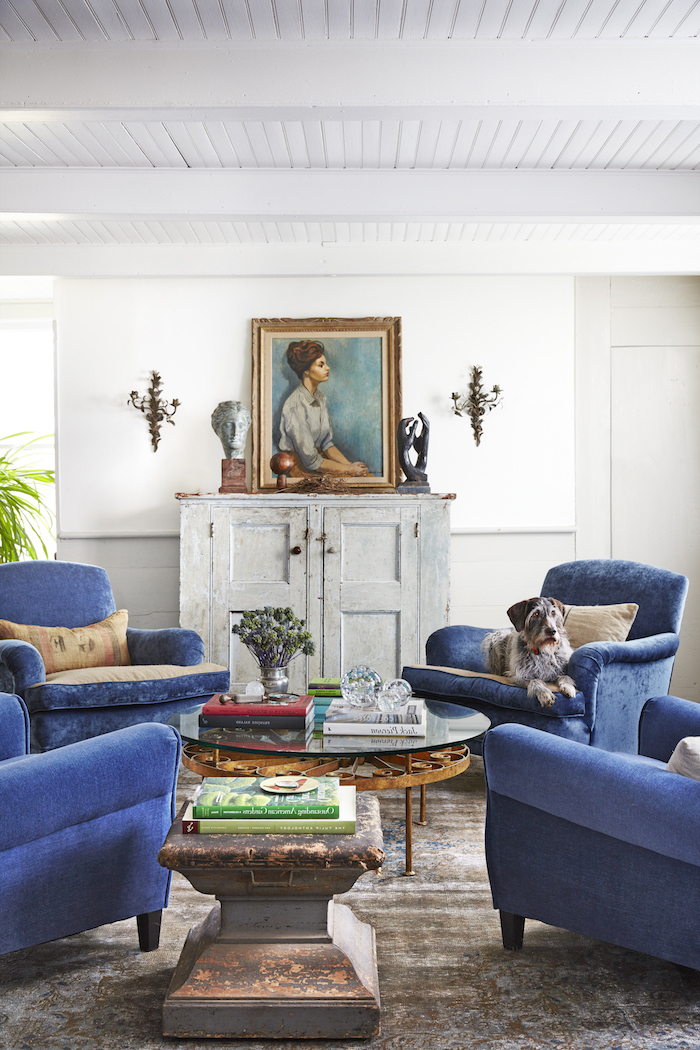 four blue velvet armchairs, glass and metal table, farmhouse decor, refurbished cabinet with framed painting on top
