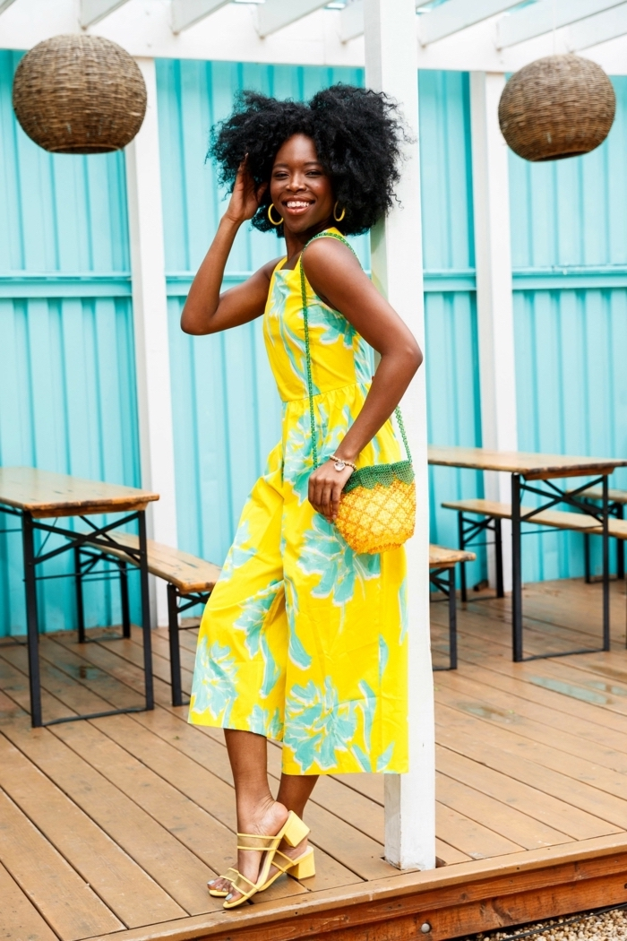 blue wall background cute outfit ideas for summer woman with black curly hair wearing yellow jumpsuit with blue flowers yellow sandals pineapple bag