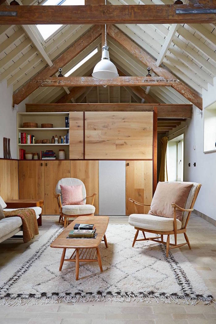 exposed wooden beams on white ceiling, farmhouse decor, bookshelf room separator, white armchairs and sofa