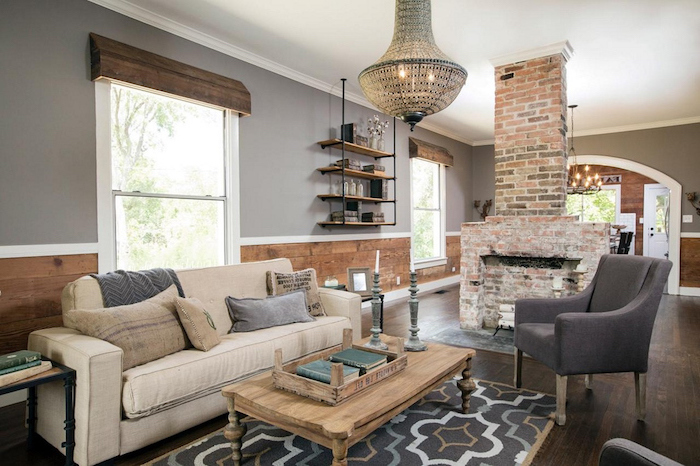 white sofa and grey armchair, wooden coffee table, modern farmhouse decor, placed in front of a fireplace, made of bricks