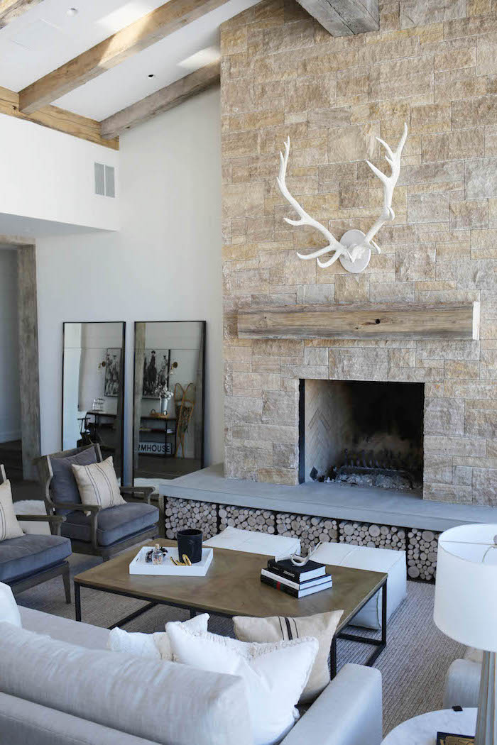 stone wall fireplace, modern farmhouse decor, grey armchairs and white sofa, placed in front of it, white carpet
