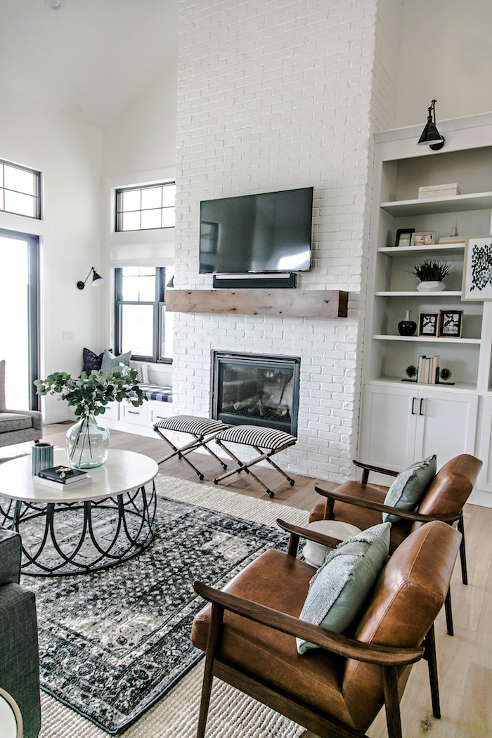 white brick wall with fireplace, farmhouse decor ideas, brown leather armchairs, white and black metal coffee table