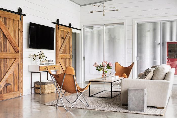two brown leather armchairs, wooden sliding barn doors, white sofa, white carpet on granite floor, farmhouse decor ideas