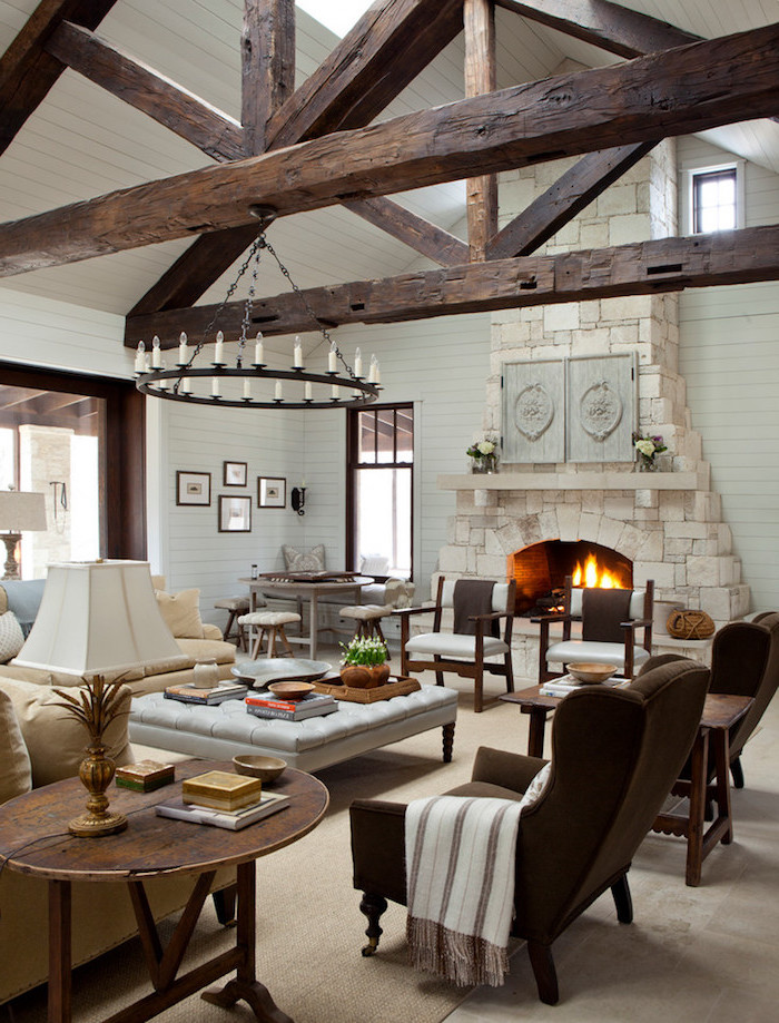 exposed wooden beams on white ceiling, farmhouse decor ideas, stone fireplace, brown velvet armchairs, white sofa and ottoman
