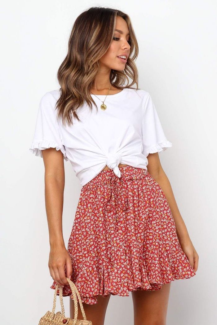 brunette woman wearing floral skirt white t shirt tied at the waist cute outfit ideas white background
