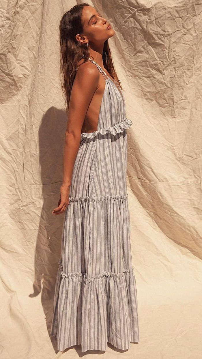 brunette woman wearing long gray pleated dress with white stripes cute summer outfits looking up