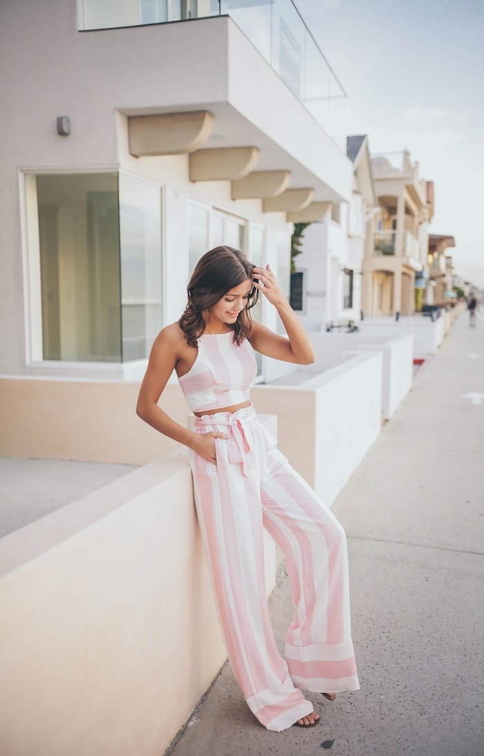 brunette woman wearing pink and white striped wide fit trousers and crop top cute casual summer outfits black sandals
