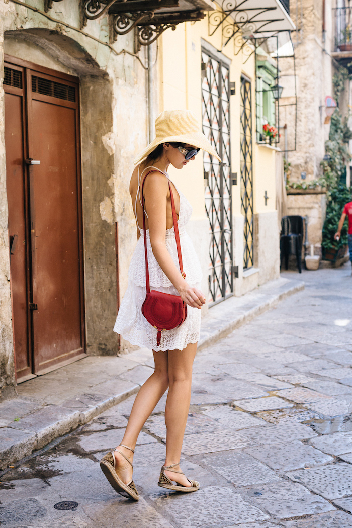 brunette woman wearing short white boho lace dress cute outfit ideas sandals and hat red bag and sunglasses