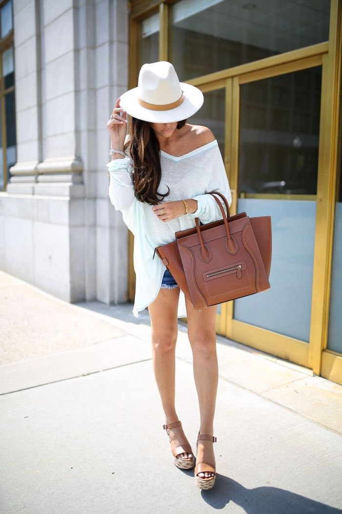 brunette woman wearing white flowy blouse jean shorts white hat cute summer outfits holding brown bag wearing brown leather sandals