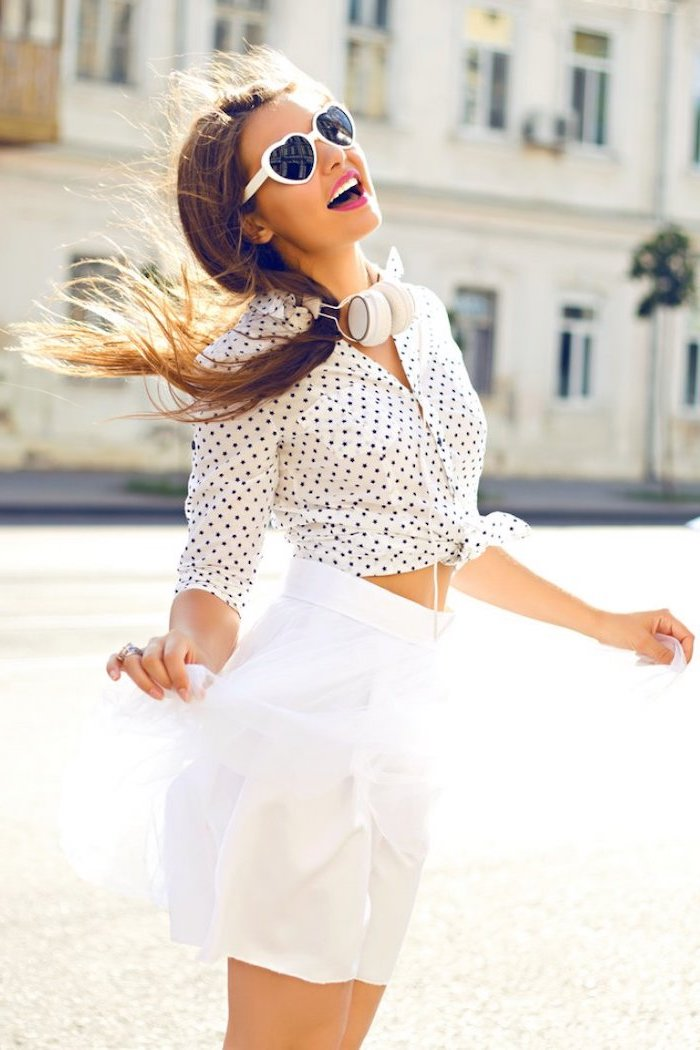 brunette woman wearing white skirt white shirt with black dots tied at the front cute trendy outfits heart shaped white sunglasses