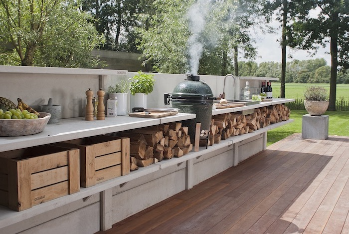 built in grill open shelves with wood logs under white countertops l shaped outdoor kitchen wooden floor