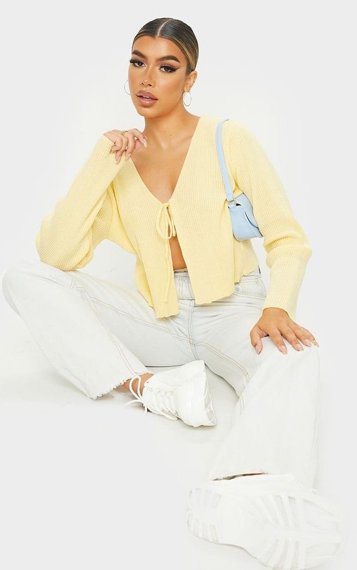 cute outfits for women woman wearing white jeans and sneakers yellow cardigan loosely tied at the front