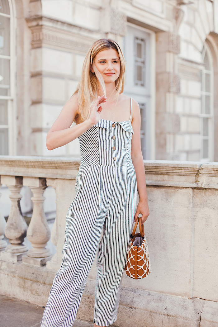 cute summer clothes blonde woman with medium length hair wearing black and white striped jumpsuit brown bag